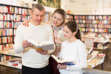 family with girl browsing books