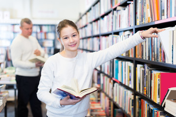 cheerful schoolgirl standing in library