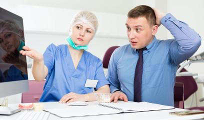 Female dentist explaining diacrisis to shocked man