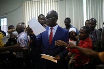 Haiti's Minister of Planning and External Cooperation Aviol Fleurant delivers copies of the statement about the resolution on the Oxfam scandal to the journalists after a news conference in Port-au-Prince
