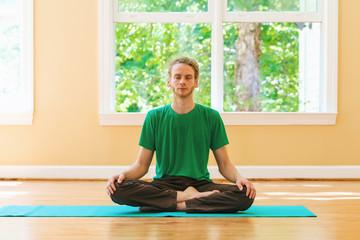 Man in a meditation pose inside a big bright room