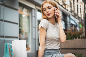 Young beautiful blonde girl with paper bags sitting at the shop window and talking on the phone