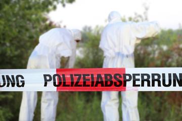 Polizeiabsperrung mit Spurensicherung im Hintergrund