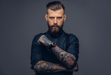 Handsome old-fashioned hipster in shirt and suspenders, pose with crossed arms. Isolated on a dark background. Wall mural