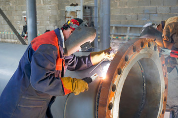 Two welders are welded, by manual arc welding, a flange DN 800 to the pipe