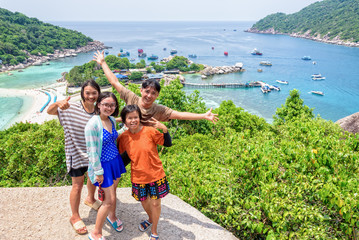 Thai family tourists is posing happily on top of the Koh Nang Yuan island is a high viewpoint and beautiful natural landscape is a famous attractions in the Gulf of Thailand, Surat Thani, Thailand