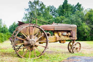Very old rusted tractor sitting in a green field under a bright blue sky in the summer time
