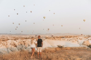 Romantic couple looking at hot air balloons in Cappadocia