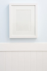 White frame mockup hanging on a blue wall with white wainscoting.