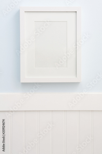 White frame mockup hanging on a blue wall with white wainscoting ...