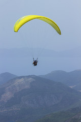 A man in a parachute is flying over the mountains. Parasailing.