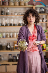 Woman asian seller in a store offers cardamom