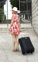 Attractive woman walking with suitcase. looking back, rear view, long legs