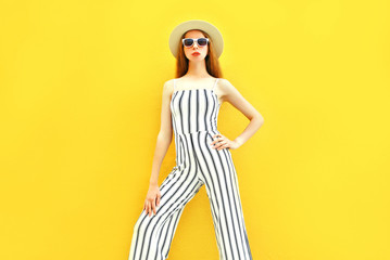 Fashion model woman is wearing a white striped pants, round hat colorful yellow background