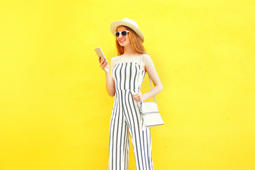 Fashion smiling woman is using a smartphone on colorful yellow background