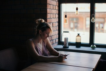 Side view portrait of young female using her smartphone sitting at the table at cafe indoors
