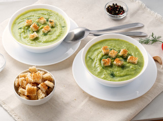 Two large white bowl with vegetable green cream soup of broccoli, zucchini, green peas on white background, side view