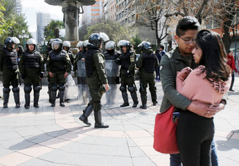 A couple is seen while riot police prepare for a protest of the students from the UPEA (El Alto Public University) in La Paz