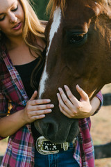 teen girl holds horse's muzzle in her hands