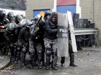 Riot police protect themselves from stones and fireworks thrown by students from the UPEA (El Alto Public University) in La Paz