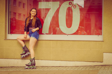 Woman wearing roller skates next to sale