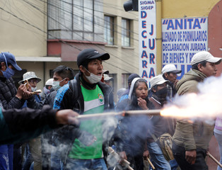 A student from the UPEA (El Alto Public University) shoots a firework during a protest in La Paz