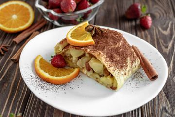 Homemade strudel with apples on a wooden background