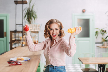 Pretty lady in shirt sitting with ketchup and mustard bottles in hands and joyfully looking in camera while spending time in cafe