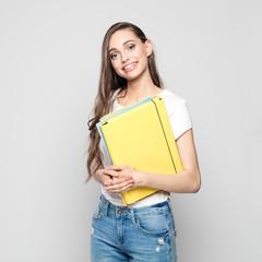 Studio portrait of happy student holding files