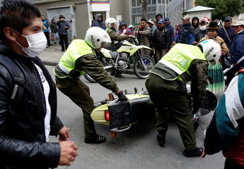 Policemen recover their motorcycle from the UPEA (El Alto Public University) students during a protest in La Paz