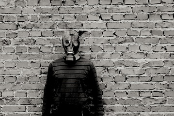 A man in a gas mask against a brick wall is black and white, contrast