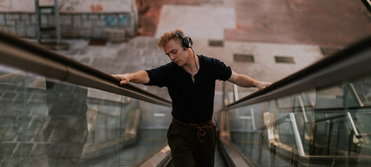 man listening to music and dancing while go up on mechanical stairs
