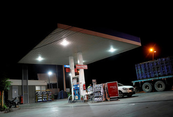 A worker fills the car at a Mobil petrol station in Toukh