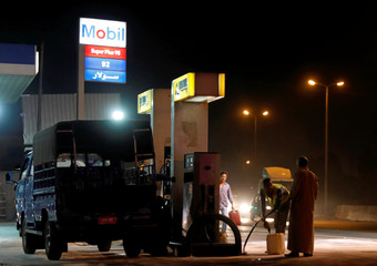 A worker fills a storage box at a Mobil petrol station in Toukh