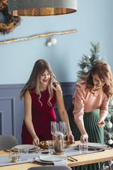 Women Setting Up Christmas Dinner Table