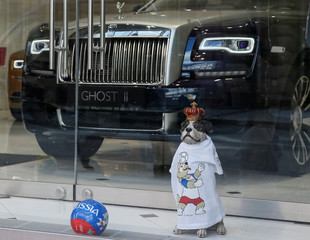 A figurine of a dog dressed in a T-shirt with a logo of the official mascot Zabivaka and a ball are seen in a show window of a luxury car salon in central Moscow