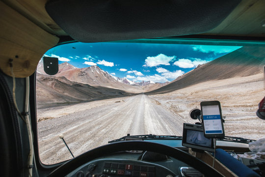 rugged dirt road with the pamir range in high altitude (4657m) seen through a windscreen of a truck
