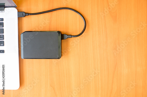 Portable external hard drive on the wooden desk near the