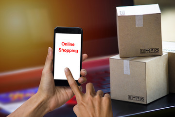 Online shopping concept e-commerce delivery buying service. square cartons shopping on laptop keyboard, showing customer order via the internet on smartphone.