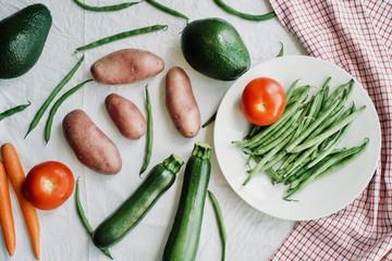 flat-lay of raw seasonal vegetables over white background. Healthy eating concept, vegetarian, vegan, clean eating.