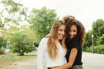 Smiling beautiful girlfriends embracing in park.