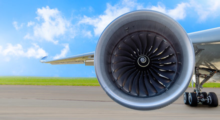 Aircraft jet engine close-up, airplane wing and chassis of landing gear wheel parked at the airport on a sky clouds background, panorama.