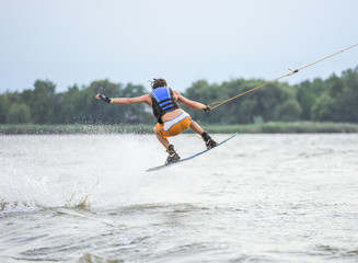 Back view of man jumping in midair with wakeboard
