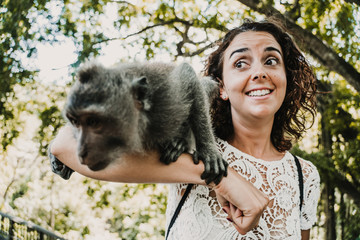 Scared funny woman taking some pictures with a cute monckey in the monckey forest in Ubud, Bali. Lifestyle. Travel photography