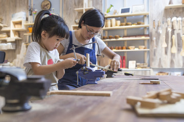 Asian womant with her kid doing carpenter job in the studio
