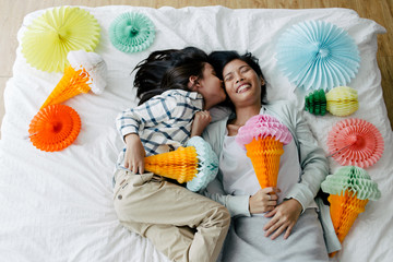Asian mother and kid having fun playing with ice-cream cone shaped tissue paper lantern decoration in the bedroom