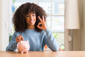 African american woman saves money in piggy bank doing ok sign with fingers, excellent symbol Wall mural
