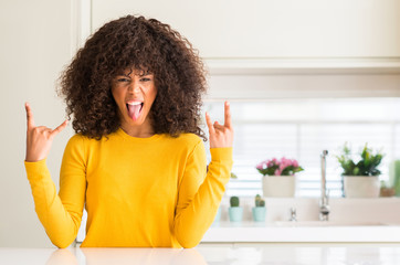 African american woman wearing yellow sweater at kitchen shouting with crazy expression doing rock symbol with hands up. Music star. Heavy concept.