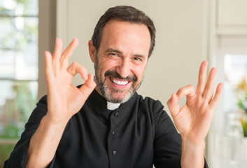 Christian priest man doing ok sign with fingers, excellent symbol