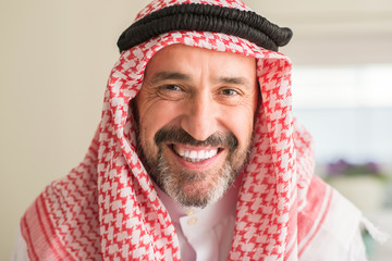 Middle age arabian man at home with a happy face standing and smiling with a confident smile showing teeth